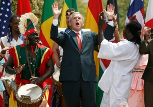 U.S. President George W. Bush dances with Senegalese dance troup during Malaria Awareness Day event in Rose Garden